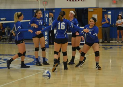 Members of the girls volleyball team congratulate each other after scoring a point.