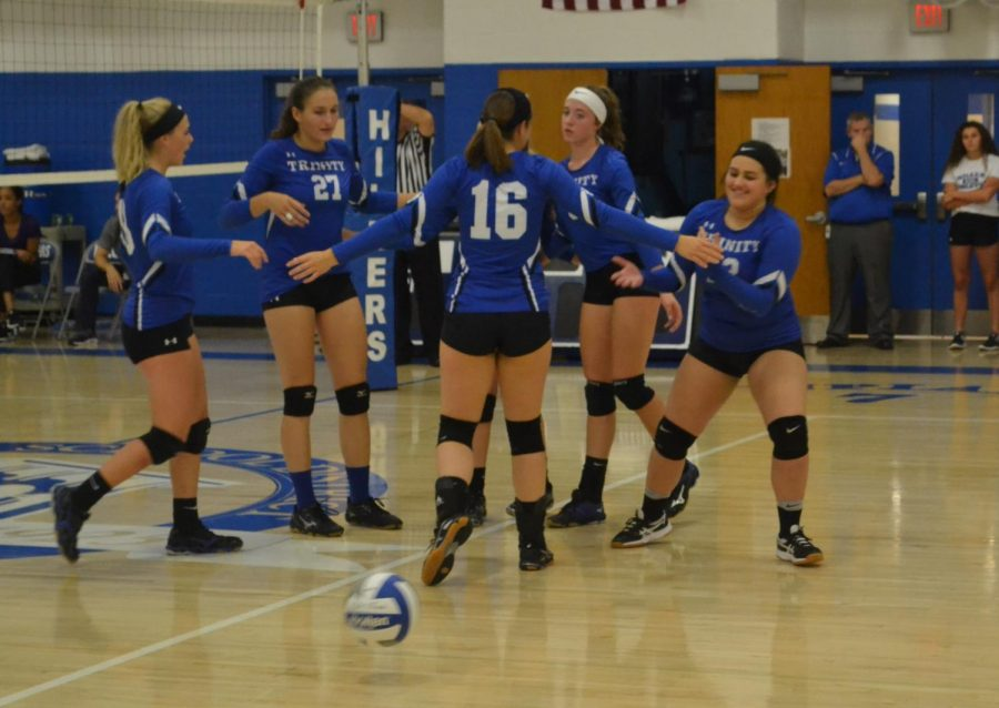Members+of+the+girls+volleyball+team+congratulate+each+other+after+scoring+a+point.