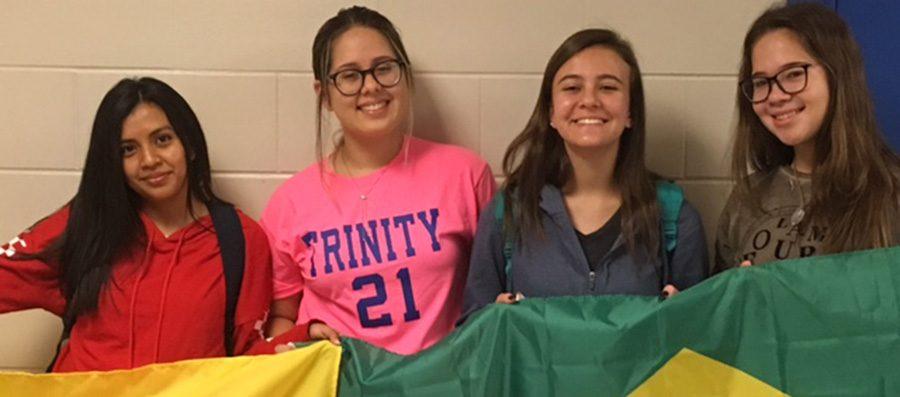 Melanny+Bastidas%2C+Maria+Edwarda+Rodrigues-Ferreira%2C+Livia+Pratera%2C+and+Nicole+Schabarum+pose+with+flags+from+Ecuador+and+Brazil.
