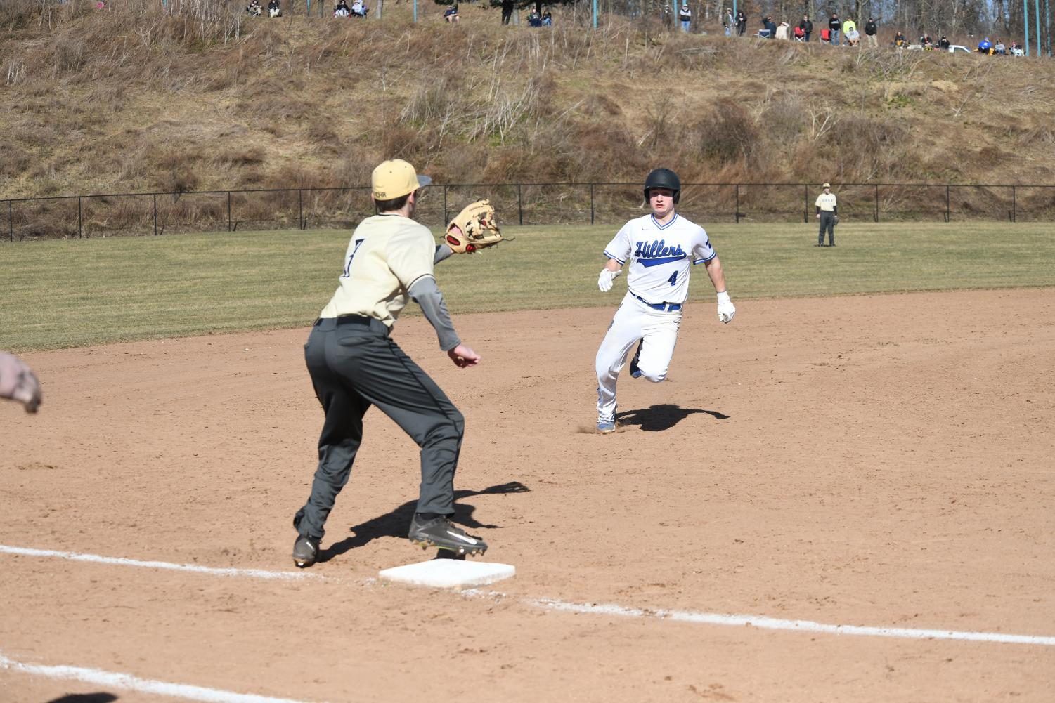 Junior catcher Jax Banco prepares himself to slide into third base in a game for the Hillers last season.