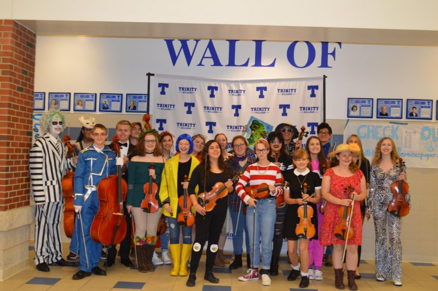 Orchestra+students+show+off+their+creative+costumes+and+pose+with+their+instruments+after+a+successful+concert.