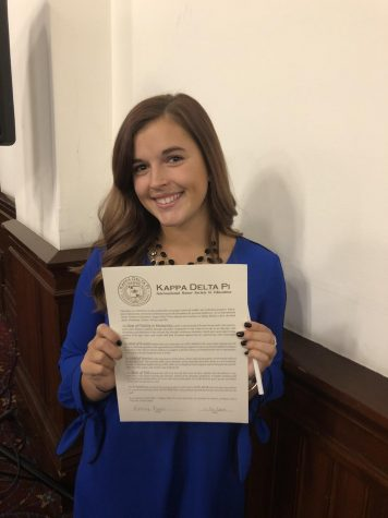 Miss Facci smiles with pride while holding her paper from the International Honor Society. She received this paper from the education department.