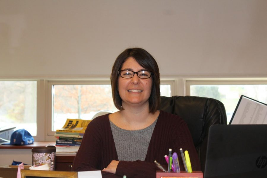 Mrs. Rush poses for a picture at her desk.