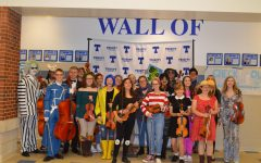Orchestra students show off their creative costumes and pose with their instruments after a successful concert.
