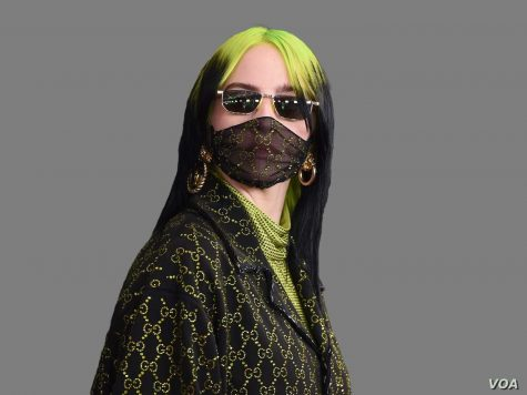 Billie Eilish poses in a Gucci suit, sporting the neon green color that is especially popular this season.