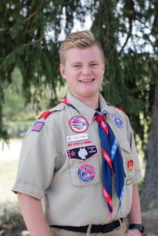Senior Colby Furman stands proudly in his scouts uniform for a senior picture. His uniform includes patches that he has earned from achievements throughout his years in scouts.