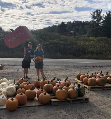 Zach and Sarah Losko stand proudly in front of their pumpkins, with their homemade signs, during a successful day of pumpkin selling.