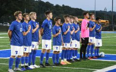 About to play, the boys began by rising for the national anthem.