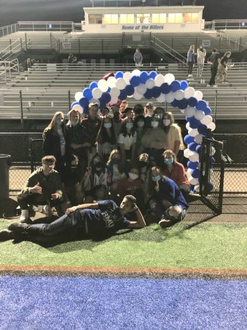 Some Seniors celebrate with a picture underneath the blue and white balloon archway.